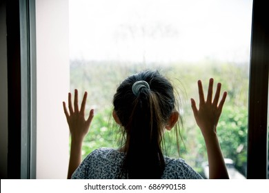 Sad little girl in room and looking out the window
