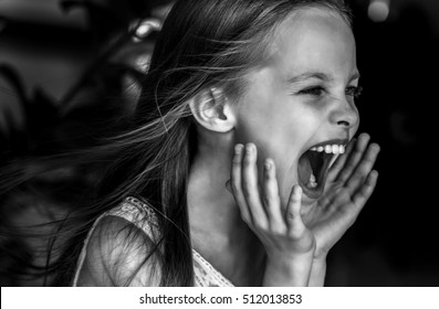 Sad little girl is  screaming indoors.  Crying kid. Facial expression.