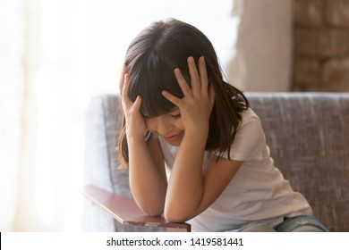 Sad little girl sit on armchair hold head in arms think or worry about something, small preschooler kid feel lonely and offended sit on chair, concerned about family problems or fight with parents