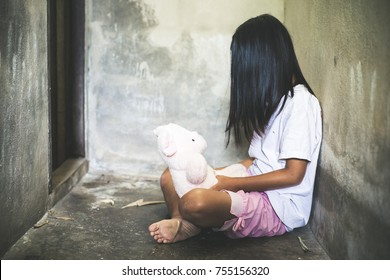Sad little girl sitting against the wall in despair.