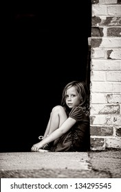 Sad, little girl sitting alone on concrete next to wall.