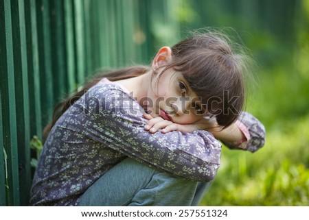 sad little girl sitting alone on stock photo edit now 257551324