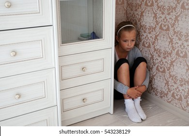 Sad little girl sitting in the corner of a room behind the cupboard