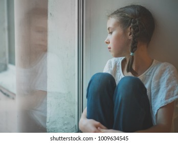 Sad little girl sitting near the window.
