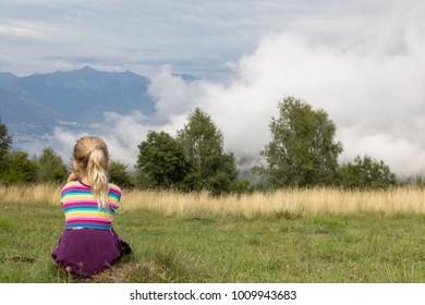 sad little girl sitting on a small rock and watching the landscape