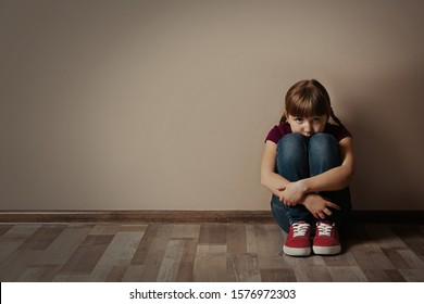 Sad little girl sitting on floor indoors, space for text. Child in danger