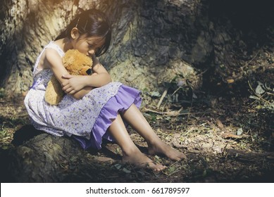 Sad little girl sitting with teddy bear under a big tree in the park, Lonely concepts.