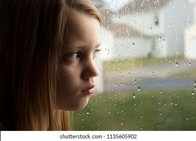 Sad little girl staring out rainy window