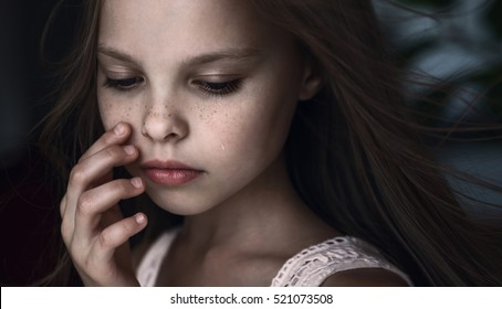 Sad little girl with tears on pretty face. Crying kid. Facial expression.