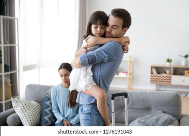 Sad little girl upset by father leaving embracing dad, depressed child saying goodbye hugging daddy going away, kid and parents divorcing breaking up, family separation, shared custody concept