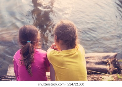 Sad little girls sitting turn back and looking at the sea at sunset