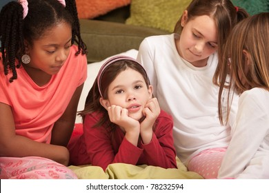 Sad little with hands on chin with friends at a sleepover
