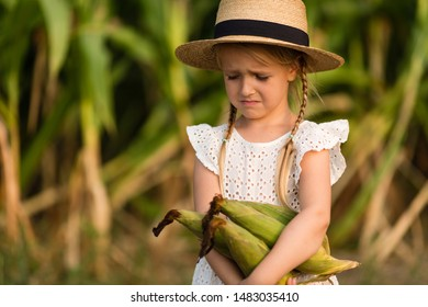 Sad Little kid in hat standing in the middle of a corn field. Harvest time. organic agriculture for children. Cute child having fun on a sunny summer day outdoor. Sun light. Happy children day concept