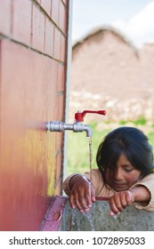 Sad little latin girl washing her hands outside.