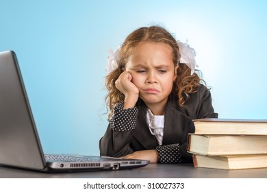 Sad Little Schoolgirl Sits At Table With Books Near Laptop On Blue Background