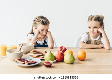 sad little sisters do not want to eat healthy breakfast isolated on white