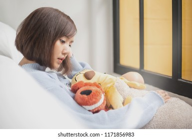 Sad and loneliness Asian woman sitting alone and hug her doll on the floor in the bedroom, broken heart concept