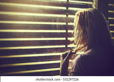 Sad and lonely blonde woman with wet hair looking through window blinds into the sunlight