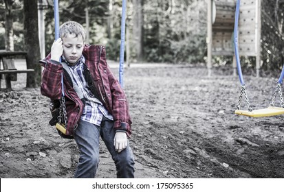 sad lonely boy sitting on swing
