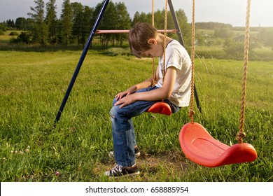 Sad lonely boy sitting on swing alone
