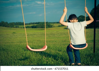 Sad lonely boy sitting on swing. Back view