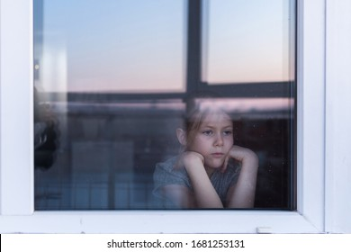 A sad, lonely child sits on the windowsill and looks out the window. Stay at home quarantine coronavirus prevention of the pandemic. The view from the street. Prevention of the epidemic.
