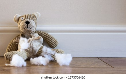 A sad and lonely child's teddy bear sitting alone on a cold floor with a ripped and torn tummy and white stuffing laying around.