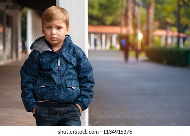Sad lonely and frustrated handsome little boy lost and standing near a pillar with his hands in his pockets in the city park.