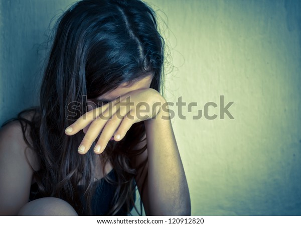 Sad and lonely girl crying with a hand covering her face (with space for text)