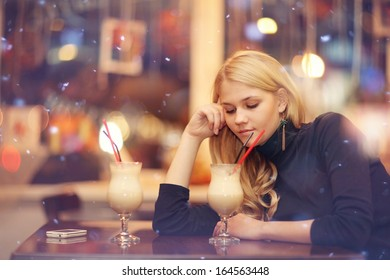 sad lonely girl drinking coffee in a cafe at night