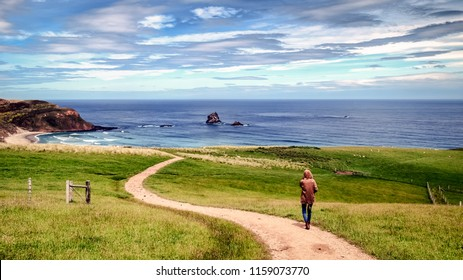 A sad lonely girl follows a narrow path towards the beach. The road is narrow and windy. The ocean is blue. The grass is lush and green. This is a great place to relax, enjoy nature and travel.