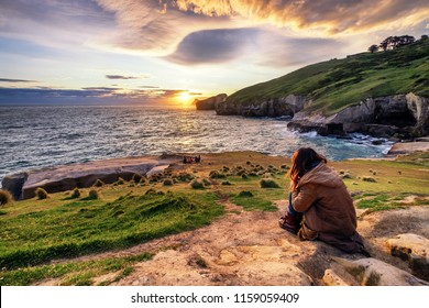 A sad lonely girl sitting on rock watching sunset. She admires ocean view, cliff, rolling hills, sunset, coves, rock formation while reflecting about the meaning of life.
