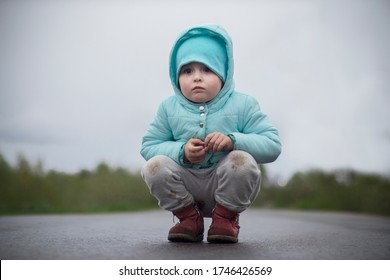 Sad lonely little baby girl, upset abandoned kid, lost child sitting or road, asphault or highway, crying in dirty clothes looking for parents, mother. Dangerous situation. Problems with children