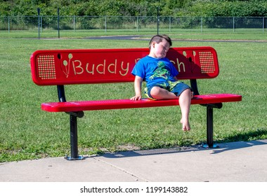 A sad lonely little boy sits on a buddy bench waiting for a friend to notice he is alone