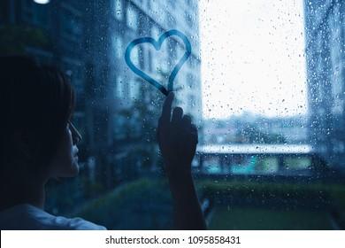 sad lonely love woman in rain draw heart on windows glass dark blue tone