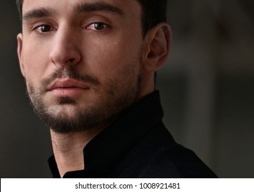 Sad and lonely man with a beautiful eyes and brutal beard standing alone in a black jacket. Handsome guy with a sexy look