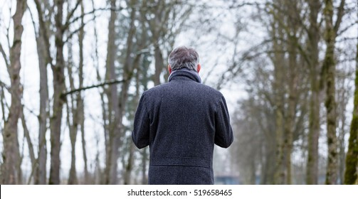 Sad and lonely man walking in winter landscape