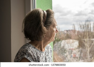 sad lonely old woman look next to  window allone depressed abandoned