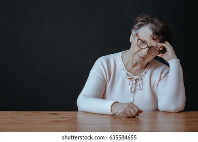 Sad, lonely senior woman sitting beside table