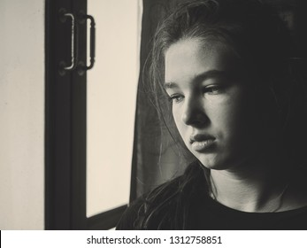Sad lonely teen girl at the window