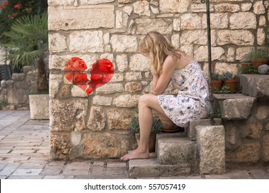Sad lonely woman with broken heart sits outside on the stone stairs in the city street, crying and covering her face.