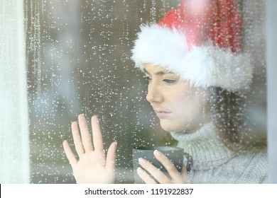 Sad and lonely woman looking through a window touching glass, with the hand in christmas time in a rainy day
