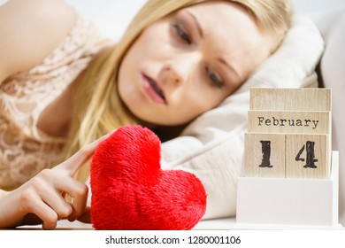 Sad lonely woman lying on bed looking at calendar, 14 Valentines day being alone with heart shape.