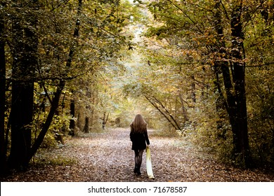 Sad lonely woman walking alone into the woods