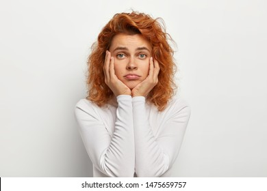 Sad lonely woman with wavy foxy hair, touches cheeks, purses lips, feels bored looks uninterested and tired, listens boring stories from friend, wears neat white turtleneck sweater. People and sadness