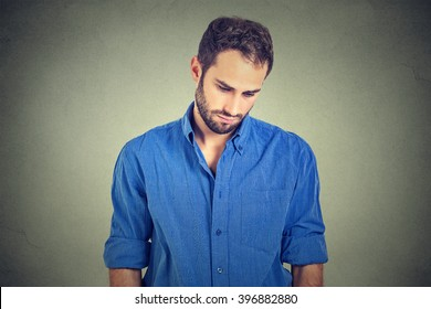 Sad lonely young man looking down has no energy motivation in life depressed isolated on gray wall background