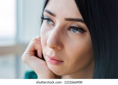 sad lonely young woman with dark hair sits and looks out the window.