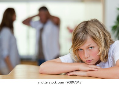 Sad looking boy with his arguing parents behind him
