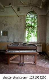 Sad looking piano at an abandoned and derelict lunatic asylum/hospital (now demolished), Cane Hill, Coulsdon, Surrey, England, UK