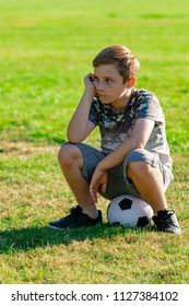 Sad looking pre-teen boy sitting on a ball. Lost game or not picked for a team concept